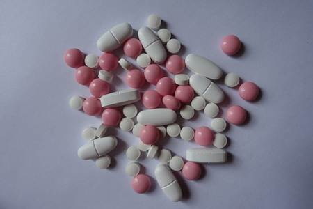 Pink and white pills of dietary supplements in a heap