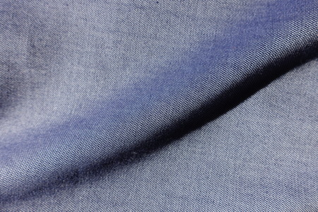 Diagonal fold on thin blue jeans fabric