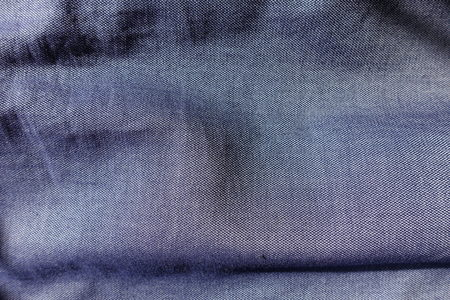 Folded blue jeans fabric shot with violet