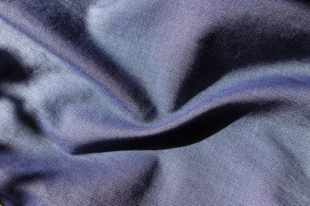 Soft folds of thin blue denim fabric