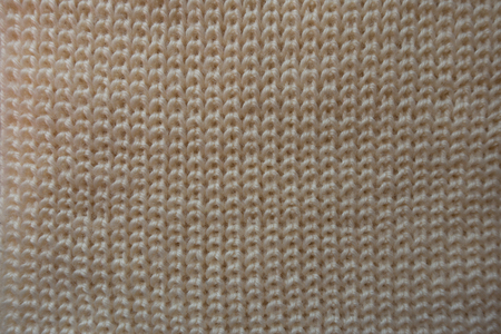 Ivory handmade knitted fabric from above (ribbing pattern)