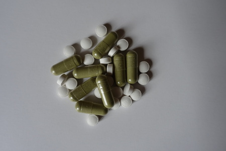 White tablets of vitamin K2 and green capsules of moringa from above