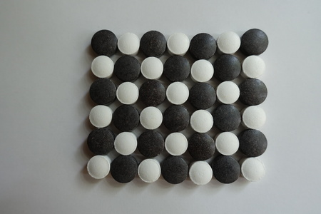 Black and white pills in shape of checkerboard from above Stok Fotoğraf
