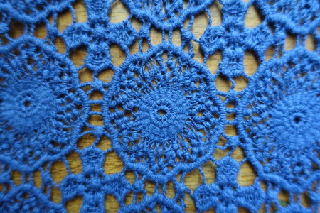 Classic blue lacy fabric on wood from above