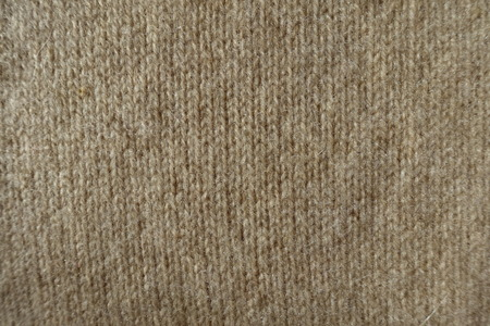 Fluffy beige handmade knitted fabric from above Stock Photo