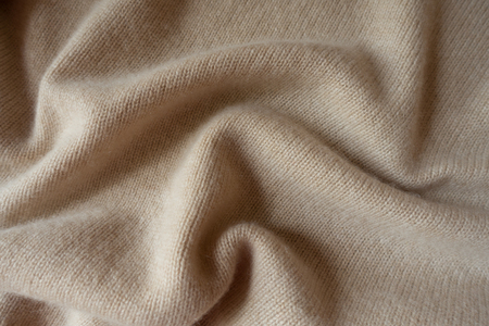 Cream colored knitted fabric in soft folds Stock Photo
