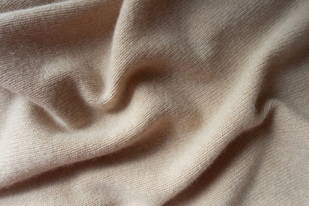 Soft folds of simple beige knitted fabric Stockfoto