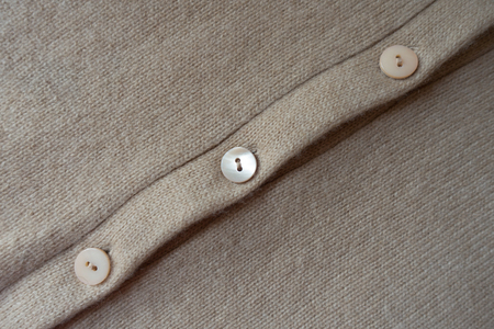 Row of buttons on simple beige knitted fabric