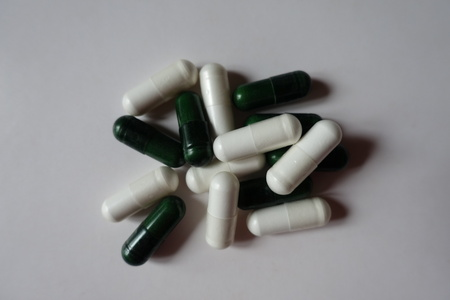 Fistful of white capsules of magnesium citrate and green capsules of multivatamins