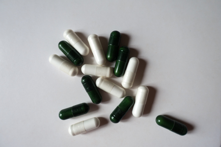 White capsules of magnesium citrate and green capsules of multivatamins from above Stock Photo