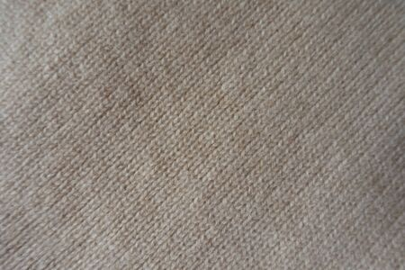 Handmade beige knitted fabric (diagonally, from above)