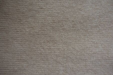 View of simple beige knitted fabric from above
