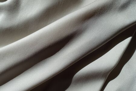 Oblique soft folds on light grey chiffon fabric