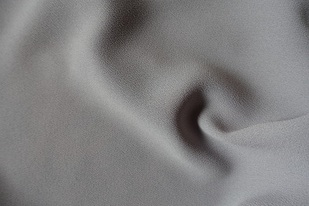 Spiral soft fold on grey crepe georgette fabric Stock Photo