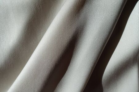 Sloping soft folds on light grey chiffon fabric