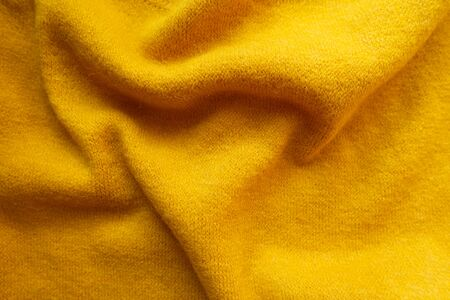 Draped bright amber yellow knitted woolen fabric from above