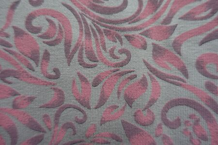 Close view of grey cotton fabric with pink scroll pattern from above Imagens