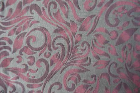 Top view of grey cotton fabric with pink scroll pattern