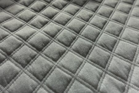 Closeup of white quilted fabric with diamonds pattern