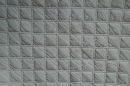 Surface of white quilted fabric from above