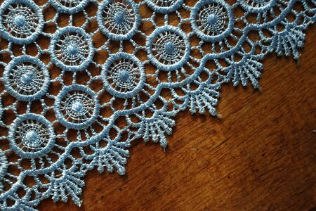 Diagonal edge of light blue crochet lace on wooden table