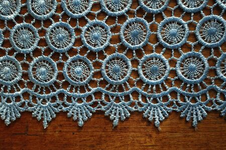 Horizontal edge of light blue crochet lace on wooden table