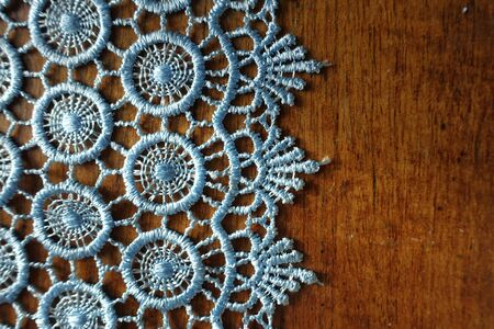 Vertical edge of light blue crochet lace on wooden table