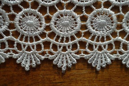 Closeup of edge of ivory white crochet lace on wooden table