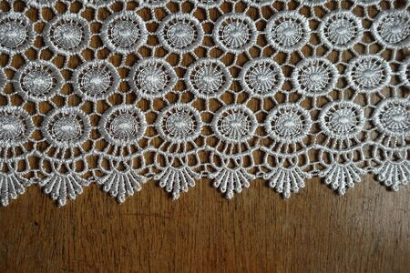 Horizontal edge of ivory white crochet lace on wooden table Imagens