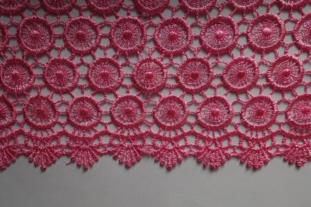 Edge of bright pink crochet lace on neutral background