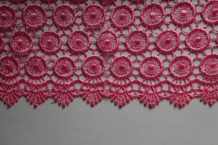 Horizontal edge of bright pink crochet lace