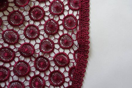 Deep red crochet lace edge on neutral background Imagens
