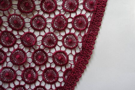 Edge of dark red crochet lace on neutral background Imagens