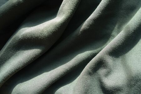 Crumpled dark green jersey fabric from above