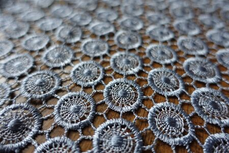 Close view of silver gray crochet lacy fabric on wood
