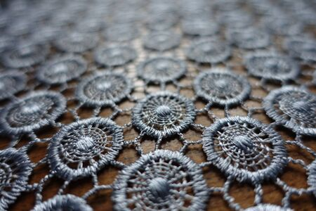 Macro of silver gray crochet lacy fabric on wood