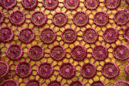 Dark red crochet lacy fabric on wood from above