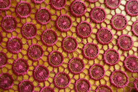 Top view of red crochet lacy fabric on wood