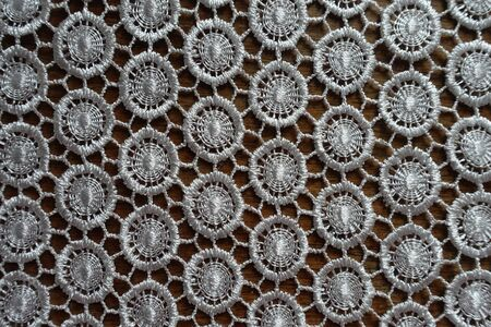 Ivory white crochet lacy fabric on wood from above 写真素材
