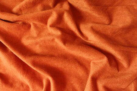 Rumpled bright reddish orange artificial suede fabric