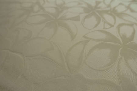 Closeup of glossy cream colored polyamide fabric with floral pattern