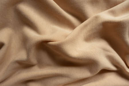 Beige cotton jersey fabric in soft folds