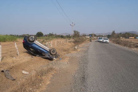 Photo of a car crashed and flipped along roadside on a road near grasslands of India