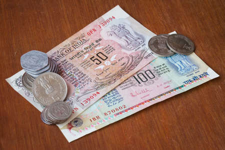 Old outdated currency placed against red wooden board Imagens