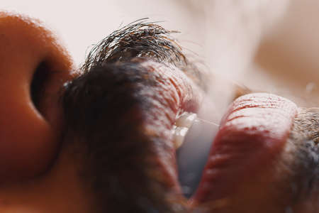 Closeup of a guy with mustache exhaling smoke from mouth