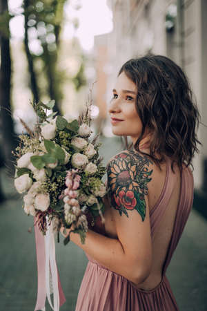 Happy and smiling woman with bouquet of flowers in a pink wedding dress and wedding ring. Bride, Bridesmaid. Modern photo style.