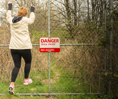 woman jumping on the fence with danger, no access sign