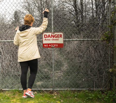 woman by the fence with danger, no access sign Stock Photo