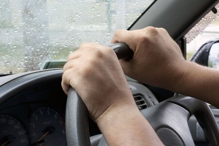 Strong mans hands on steering wheel photo