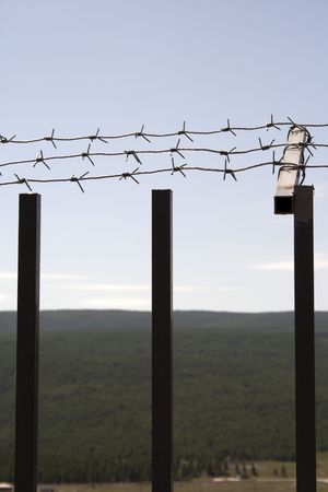 Fence with a barbed wire on a background of blue sky photo